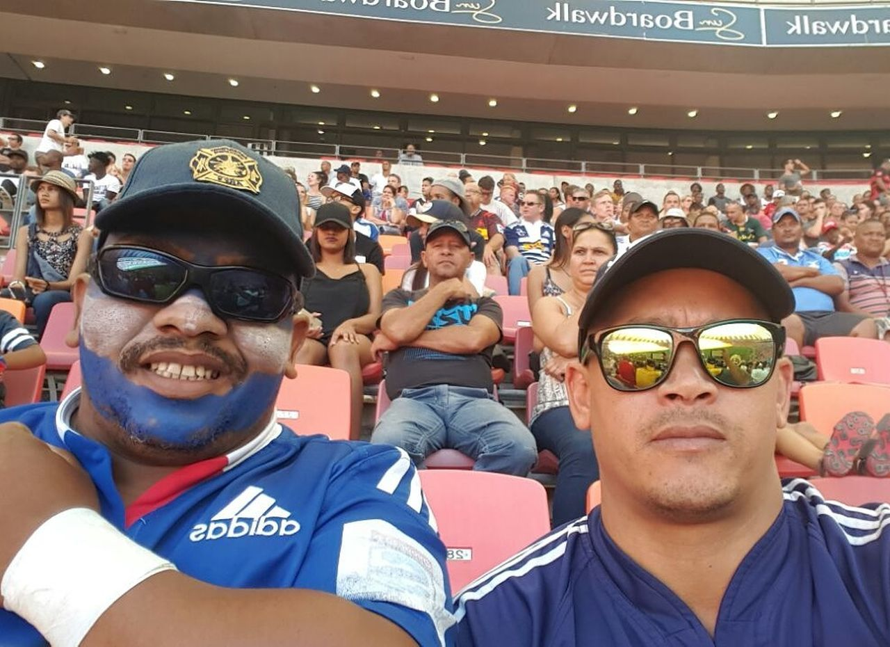 sunglasses, arts culture and entertainment, crowd, leisure activity, real people, large group of people, young men, young adult, togetherness, smiling, stadium, looking at camera, day, enjoyment, performance, portrait, audience, happiness, sport, lifestyles, outdoors, fan - enthusiast, people, adult