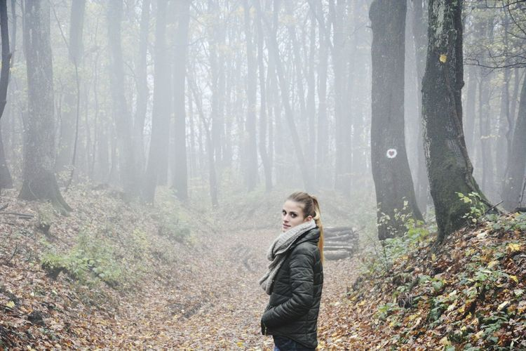 Side View Portrait Of Woman Standing In Forest During Foggy Weather