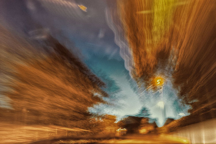 Blurred motion of illuminated car against sky at night