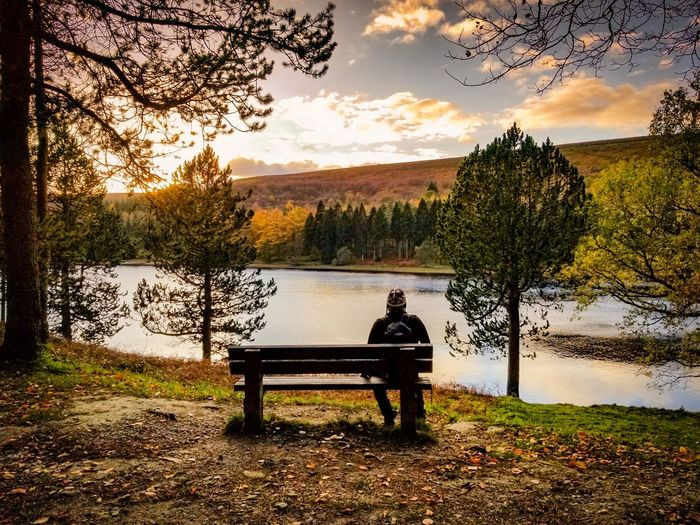 Man sitting on bench by river against sky