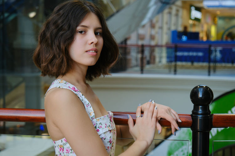 Portrait of woman against railing