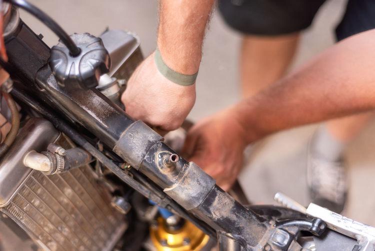 Cropped hands repairing motorcycle