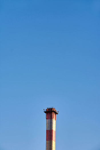 Low angle view of smoke stacks against clear blue sky
