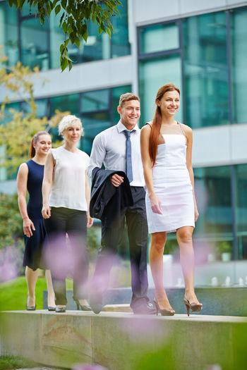 Business People Walking Against Building