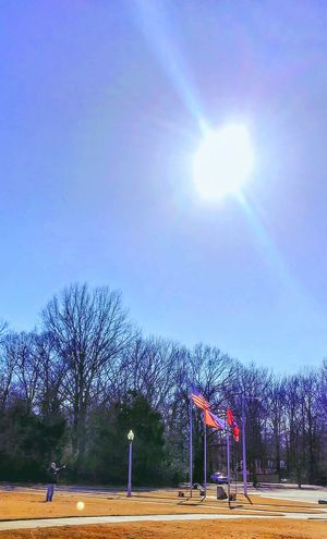"Flying the ""invisible"" kite... can't see it for some reason American Flag Flags In The Wind  At The Park Flying A Kite Sunshine ☀ Outdoors Orb Orbs Clouds And Sky Light Tree Silhouettes Sky Day"