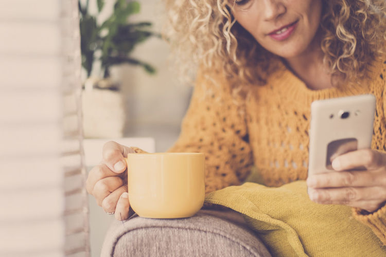 Nice blonde curly middle age woman at home drinking tea or coffee and using cellular phone with internet technology web search for leisure or business work activity - people relaxing during the day One Person Holding Technology Wireless Technology Mobile Phone Young Adult Cup Communication Connection Women Hair Adult Lifestyles Smart Phone Real People Mug Coffee Cup Sitting Young Women Hairstyle Hot Drink Outdoors Females Smiling Breakfast Break Tea Relaxing Yellow Color Blogger Reading Curly Hair Beautiful People 40-44 Years Sunlight