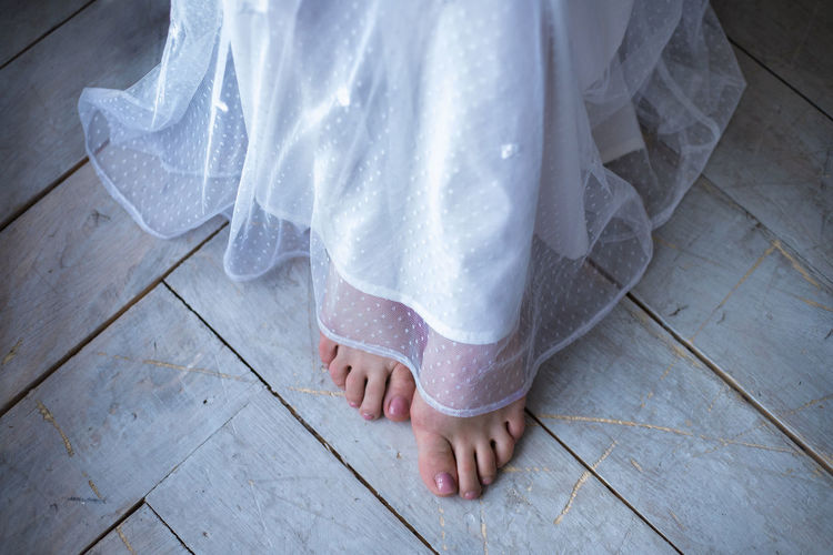 Low section of bride wearing wedding dress