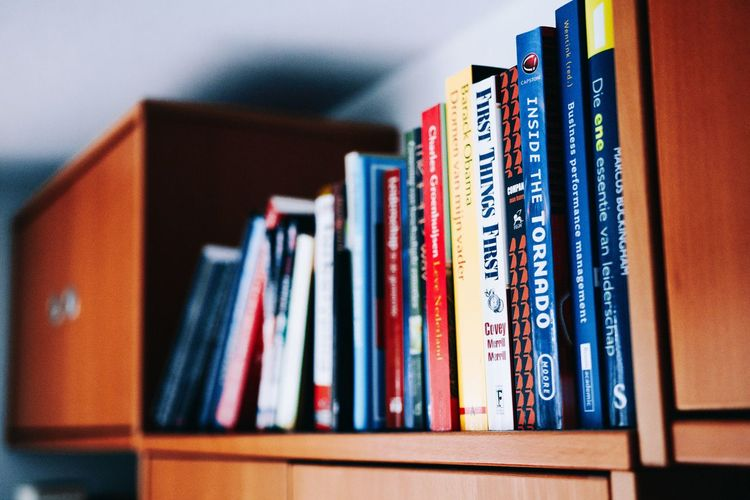 Close-up of books in shelf at home