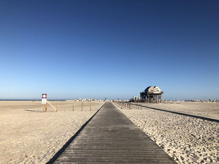 Rear view of man on pier at beach against clear blue sky