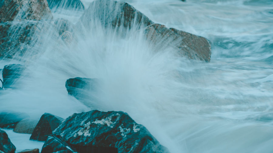 Close-up of sea wave splashing on rock