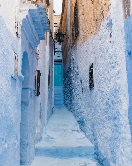 Footpath Amidst Buildings In Snow