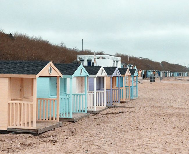 Beach huts in row against sky