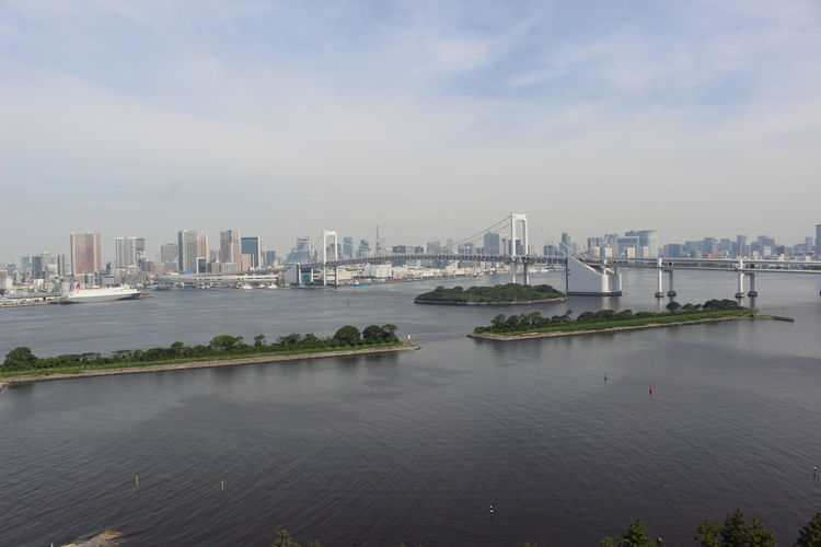 Scenic View Of City By River Against Sky