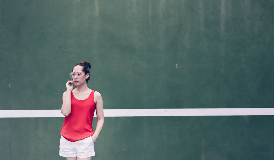 woman wear glasses fashion in tennis court Sport One Person Standing Young Adult Lifestyles Sports Clothing Front View Three Quarter Length Women Healthy Lifestyle Athlete Exercising Adult Day Copy Space Leisure Activity Tennis Clothing Contemplation Fashion Art Check This Out Posing