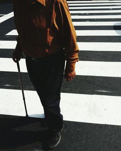 Low Section Of Senior Man With Walking Cane On Road