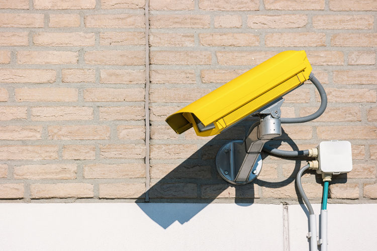 Close-Up Of Security Cameras On Brick Wall