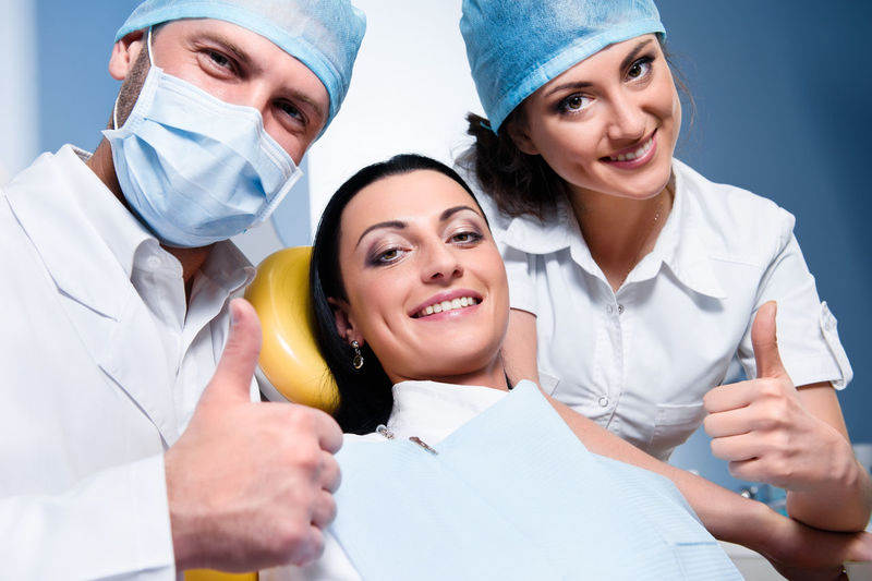 Portrait of confident doctors with patient showing thumbs up in dental clinic