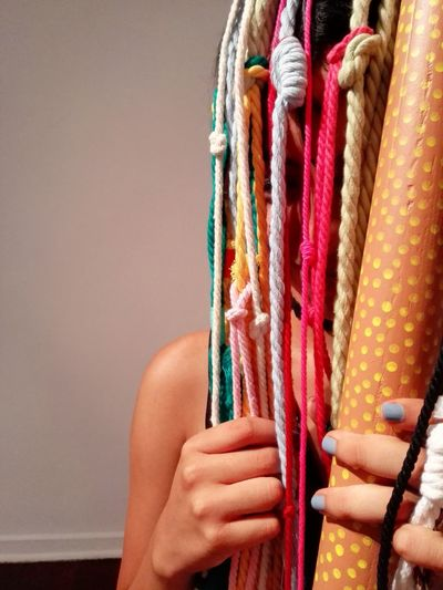 Close-up of woman hiding behind colorful strings against wall
