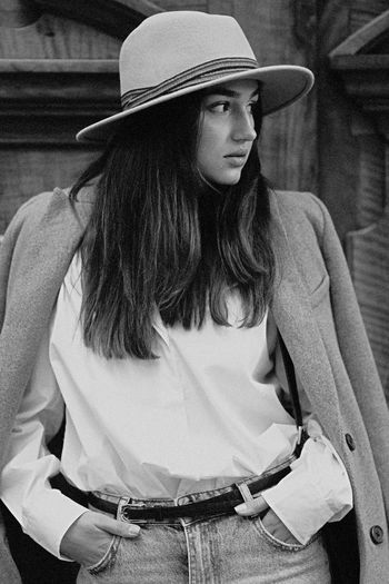 Young woman wearing hat looking away outdoors