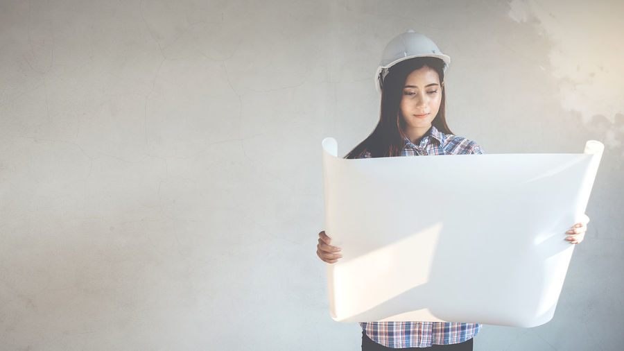 White Helmet Female Architect Holds Blueprint While Examining Building Jobs Architecture Construction Attractive Blueprints Builder Helmet Safety White
