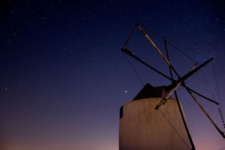 Low angle view of wind turbine against star field at night