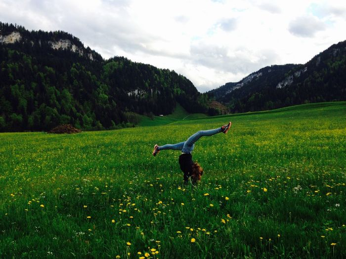 Woman Dancing On Grassy Field By Mountains Against Sky