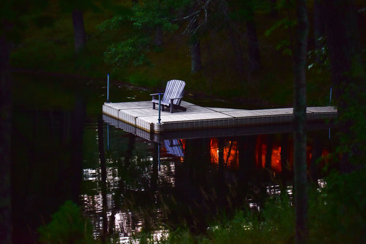 Empty Adirondack chair bench on dock at night over water Water Nature Lake Outdoors Tree No People Forest Beauty In Nature Sunset Dusk Pond Chair Furniture Outdoor Chair Bradley Olson Bradleywarren Photography Adirondack Chairs Landscape Lake View Scenics Copy Space Room For Copy Room For Text Relax Tranquility