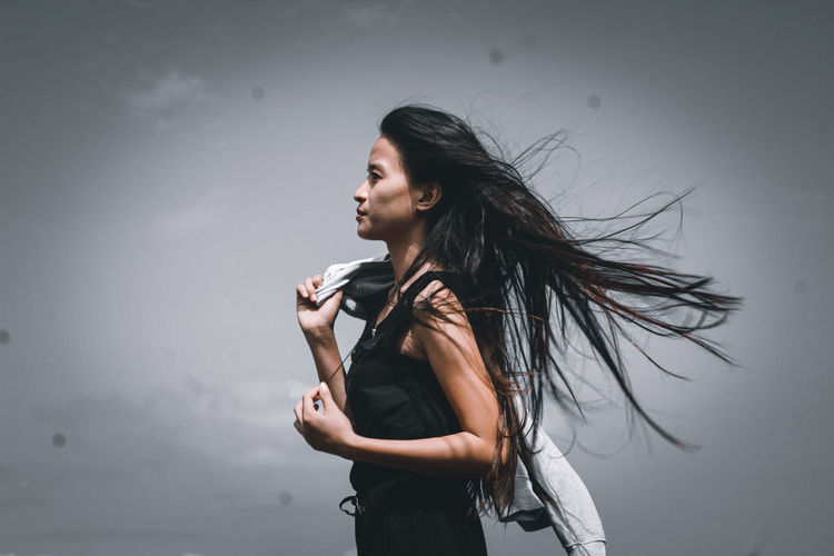 Young woman looking away while standing against sky