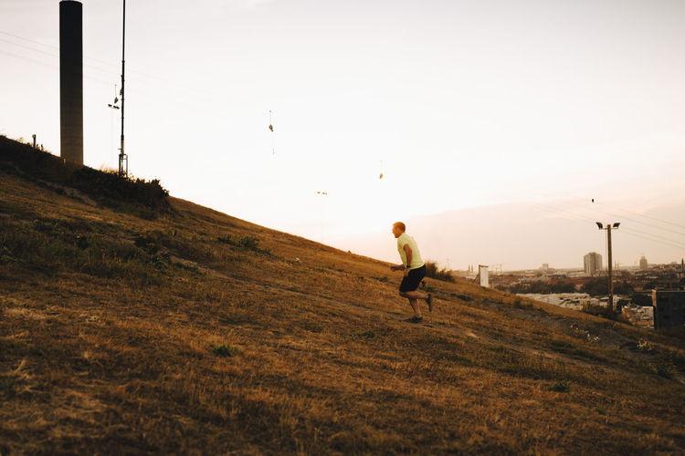 Full length of man on field against sky during sunset