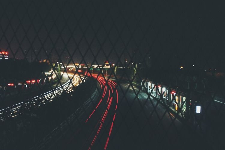 High angle view of light trails on road seen from chainlink fence at night