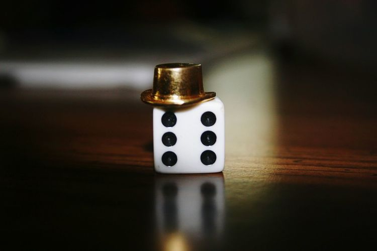 Close-Up Of Dice With Toy Hat On Wooden Table