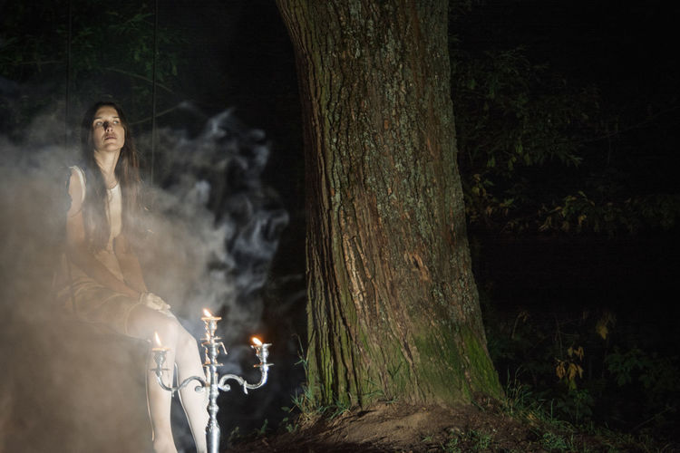 Woman sitting by tree trunk with candles in forest