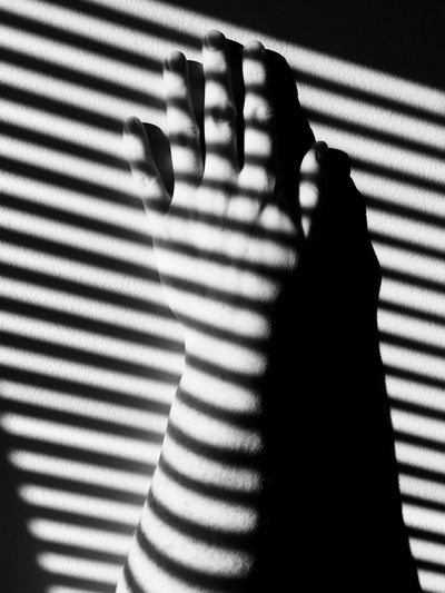Cropped image of woman hand with shadow pattern on wall