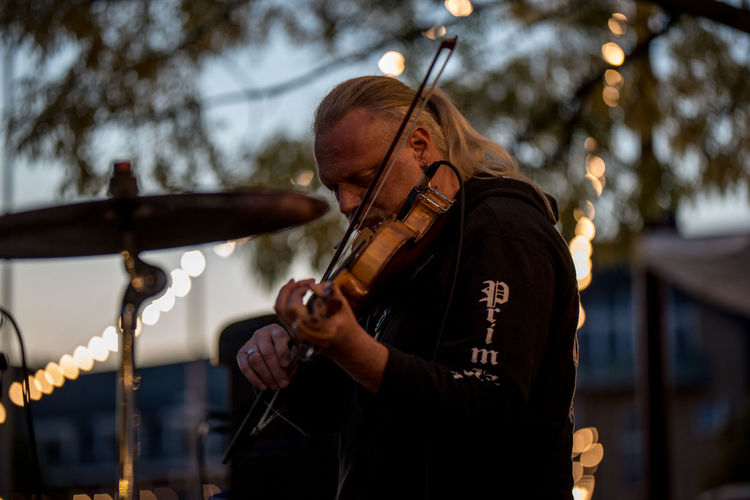 Side view of man playing violin against tree during sunset