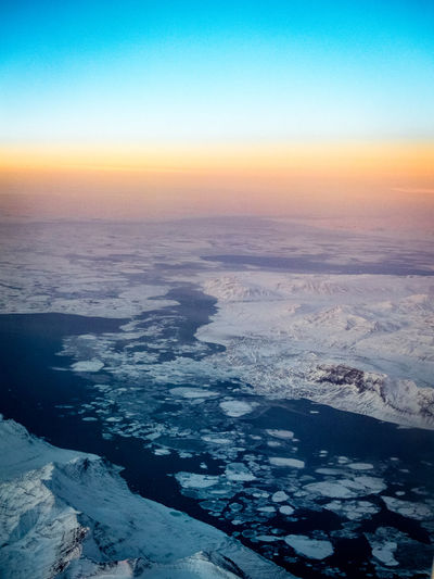 sunrise high over greenland Aerial View Arctic Arctic Ocean Beauty In Nature Blue Blue And Orange Blue And Orange Sky Clear Sky Cold Temperature Dawn Dawn Of A New Day Eternal Ice Flying Greenland Ice Ice Floe Ice Floes Ice Sea Mountain Range Nature Polar Sea Scenics Sea Sunrise Tranquil Scene