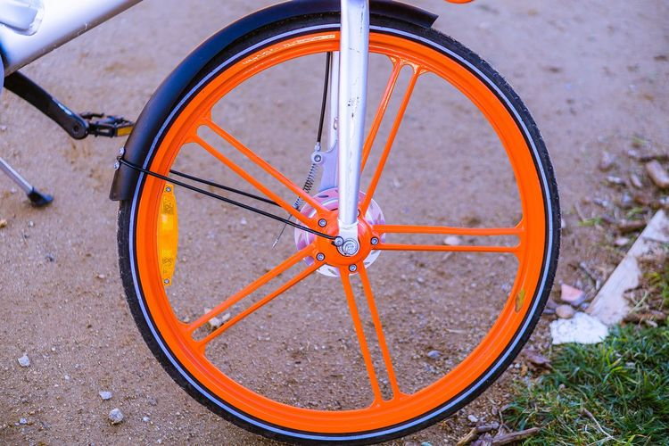 Nature No People Day Outdoors Sunlight Sun Wheel Transportation Bicycle High Angle View Land Vehicle Mode Of Transportation Metal Street Focus On Foreground Road Orange Color Tire Close-up Stationary Field Circle Spoke Outdoor Play Equipment