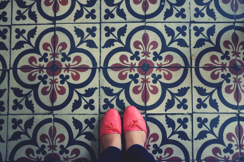 Low section of woman standing on floral pattern floor