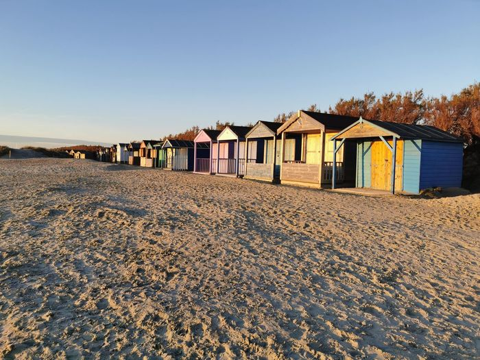 Beach huts by buildings against clear sky