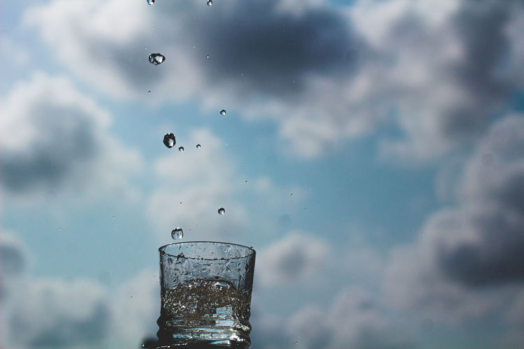 Close-up of water drops on glass against the sky