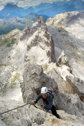 High angle view of woman climbing on rock against mountains