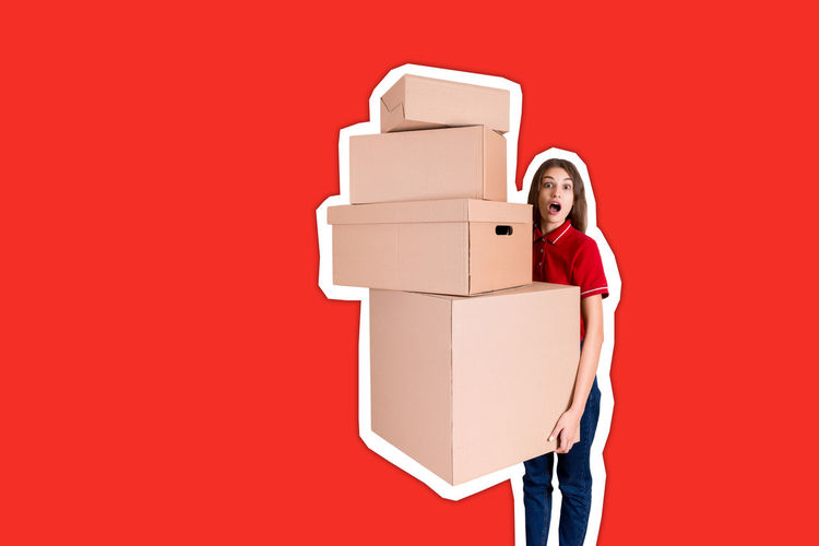 Full length of a woman holding stack against red background