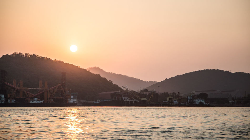 sunset over sea with cargo ships Cargo Ship Architecture Beauty In Nature Building Exterior Built Structure Clear Sky Day Idyllic Landscape Mountain Mountain Range Nature No People Outdoors River Scenics Silhouette Sky Sun Sunlight Sunset Tranquil Scene Tranquility Water Waterfront