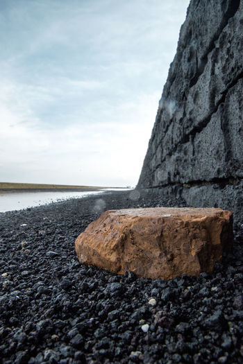 Stone wall by sea against sky