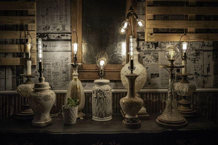 Illuminated electric lamp hanging at night
