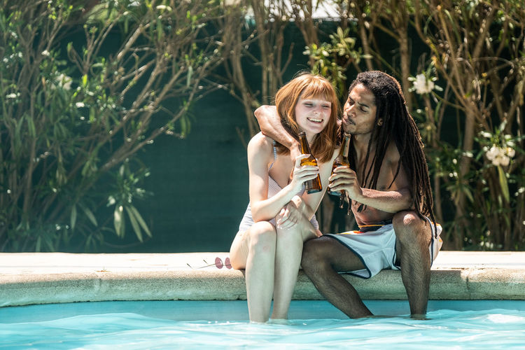 Couple toasting beer bottles while sitting at poolside
