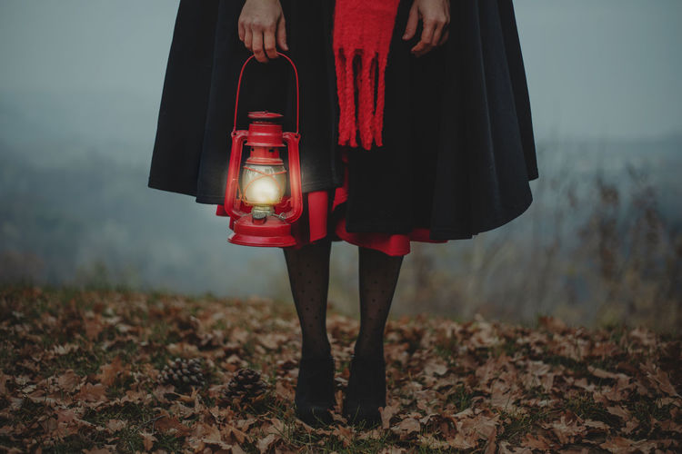 Low section of woman with red lantern