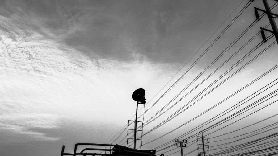 Low angle view of megaphone and electricity pylon against sky