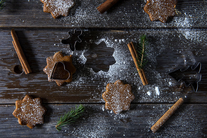 Directly above shot of powdered sugar over cookies and cinnamons on wooden table