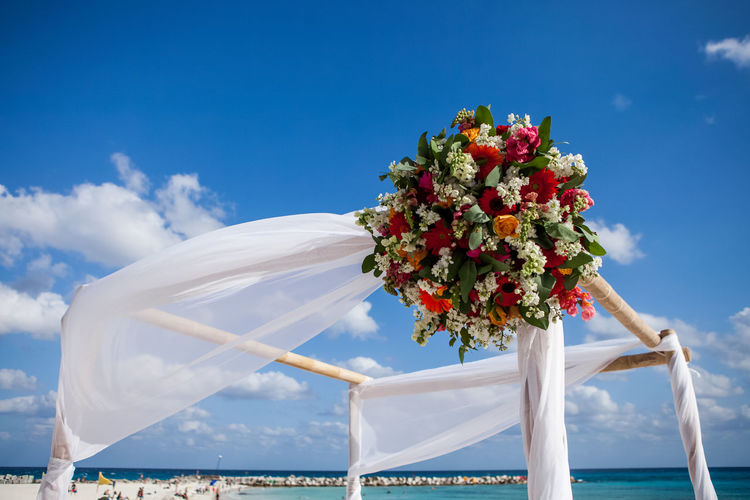Low angle view of bouquet hanging on entertainment tent at beach against blue sky