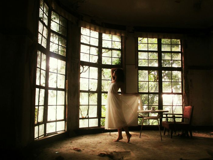 Teenage Girl With Arms Raised Standing In Abandoned House